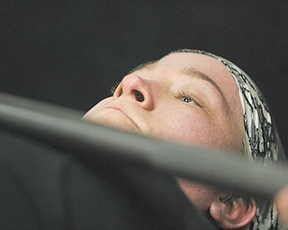 Chelsi Figley grimaces as she practices the bench press. The 27-year-old East Palestine resident, who is afflicted with spina bifi da, will compete in the Paralympic Games in Malaysia later this year.