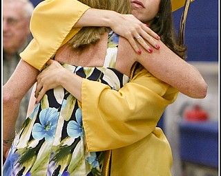 ROBERT K. YOSAY | THE VINDICATOR..Congratulatory hug from a friends mom is Jami Hynes ( in gown ) hugging Liz Ciarniello ( flowered dress).at Lowellville High School gym - the glass of 2010 - graduated Sunday afternoon-30