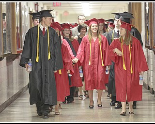 LESLIE CUSANO | THE VINDICATOR.Excited Canfield High School graduates walk down the athletic hallway at the high school before commencement exercises Sunday.