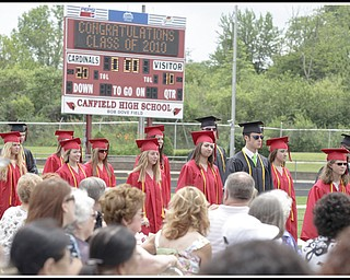LESLIE CUSANO | THE VINDICATOR.Canfield High School graduates process onto the Bob Dove Field during commencement exercises Sunday.