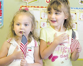 Clara Carriocce, left, and Michelle Queen, both 4, recite the Pledge of Allegiance at Lads 'N Lassies. Today is National Flag Day, established by Congress in 1949 to commemorate the anniversary of the adoption of the U.S. flag in 1777.