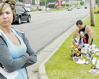 Ashley Bleggi, girlfriend of Nicholas Stubler, a motorcyclist killed in a weekend crash on South Avenue, Boardman, pauses at a roadside memorial at the crash site. Jamie Milsom of Leetonia, a friend of Stubler's, pays his respects in the background.
