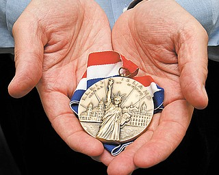 Tom Cook holds his 2010 Ellis Island Medal of Honor.