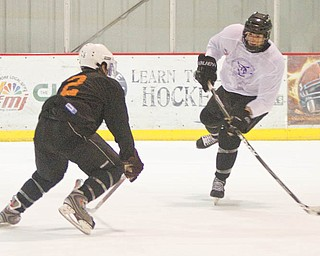 Dylan Margonari (12) successfully scores a goal past Jordan Young (2) during the first period of a scrimmage at the Ice Zone on Tuesday evening.