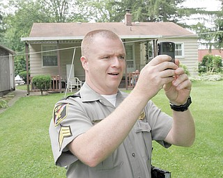 Poland Village Police Sgt. Jim Craven snaps a picture of the black bear that roamed behind homes on Mathews Road.