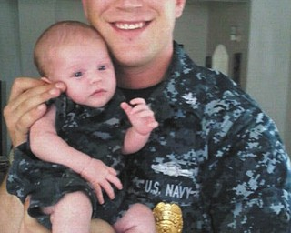 Christopher Holtzman, formerly from Poland and now stationed at Naval Air Station in Pensacola, Fla., holds his newborn son, Christopher.