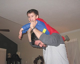 "Nathan Richley, 3, and his father, Joseph Richley of Poland demonstrate how ""My Daddy helps me fly like Superman."""