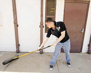 Dante Dutch, 17, helps in Monday's cleanup near Neighborhood Ministries in Campbell.