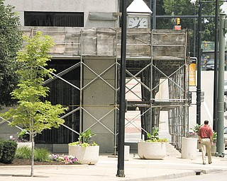 A pedestrian makes his way around scaffolding on the PNC Bank Building on Central Square in downtown Youngstown. The scaffolding was supposed to come down months ago, and the city is considering suing the buildingÕs owner to get it removed.