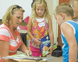Melissa Cherne of Boardman and her children, Morgan, 7, and Tyler, 4, pick out books illustrated by Cyd Moore. The family is a fan of MooreÕs ÒI Love You, Stinky FaceÓ book..