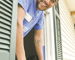 Bike & Build volunteer Hassam Shalla of Philadelphia checks out a window at the Mahoning County Habitat for Humanity house under construction on Maranatha Drive in Youngstown.