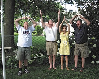 2010 Ohio State University graduate Anne Garwig of Columbus celebrates at her graduation party by forming the ÒOhioÓ pose with, from left, her father, Glen Garwig of Boardman, and her uncles, the Rev. Robert Garwig of Portland, Ore., and John Garwig of Cleveland, at the Garwig home in Boardman.