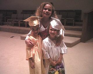 Big sister Delia Walkowiec, 9, congratulates brother Zenin, and classmate Maria Slaton, 5, of Austintown at preschool graduation from For Kids Sake.