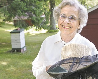 """Mary Brashen, a beekeeper for some 30 years, stands near one of her five bee hives at her home in Hubbard Township. Brashen, who puts the tag of """"Merry Bee"""" on her jars of honey, recently was called to Hubbard Area Library to collect a swarm. ."""