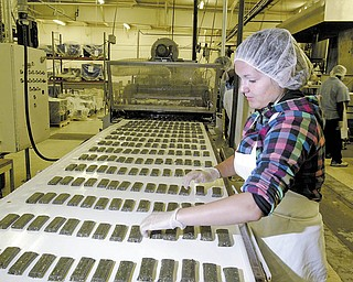 Karen Brendlinger, an employee at Belmont Confections, checks 4LifeBars as they come down a conveyor belt.