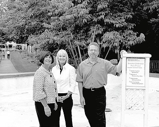 In no danger of getting their feet wet as they stand in the basin of the old K. Calvin Sommer Fountain in Fellows Riverside Gardens, where a new fountain will be built are, from left, Sharon Letson, garden party chairwoman; Pati Opalka, co-chairwoman, and Keith Kaiser, horticulture director at Mill Creek MetroParks.