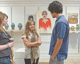 From left, Halley Snow of Youngstown, Nikki Mehle of Canfi eld and Justin Reese of Youngstown chat around their artwork displayed at the Art Outreach Gallery at Eastwood Mall. Their teacher is Kathy Young.