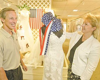Mark and Lorraine Fulks, owners of Treasured Moments Bridal and Formal in Boardman, show off bridal gowns. The store will participate on Friday in Brides Across America, a non-profit program that distributes free gowns to military brides.