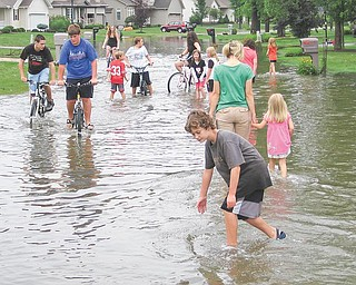 Neighborhood kids wade through water on Laura Lane in Cortland on Tuesday afternoon. Three hours after a burst of rain hit the neighborhood, parts of Laura and a nearby street were still flooded.