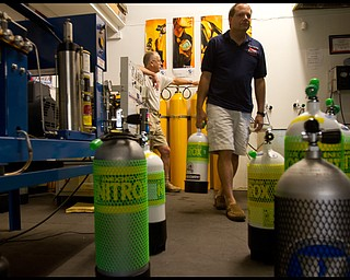 Geoffrey Hauschild|The VIndicator.Director of Training, Shawn Campbell, carries tanks away from a filling area at B&B Diving in Hillsville PA. Campbell reccomends Nitrox which has 50% more oxygen than tanks of compressed air.