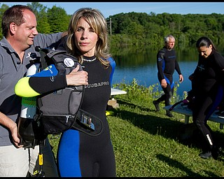 Geoffrey Hauschild.Director of Training, Shawn Campbell, helps his wife, Aimee Campbell, both of Union Twp., suit up with her equipment at B&B Diving in Hillsville PA.