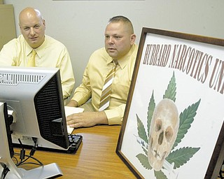 Patrolmen Mike Pieton, left, of Hubbard Police Department and Ronald Fusco of Hubbard Township Police Department work in the Hubbard Narcotics Unit offi ce in the township department. A logo for the unit relays the deadliness of drug use. ITT Technical Institute in Youngstown donated the computer and furniture for the office.