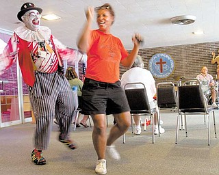 Event coordinator Brenda Mack of Canfi eld dances with J.J. Losasso, a resident of Boardman and member of Aut Mori Grotto, during the Midlothian Free Medical Clinic festival Sunday afternoon.