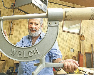 Richard Zitto of Columbiana displays a classroom demonstration Micrometer, part of his large collection of teaching devices for physics classes. The former Boardman High School and Youngstown State University instructor is giving the Smithsonian Institution 171 pieces of his collection.