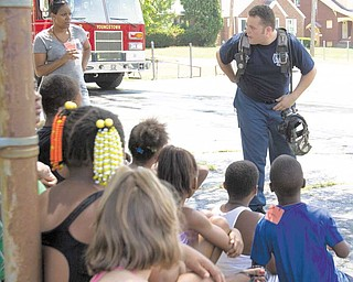 Children participated this week in the summer camp Thursday at Martin Luther Lutheran Church, 420 Clearmount Drive, Youngstown. Among activities this week for the children age 6 to 15 were Bible stories, music and crafts. Here, firefighter Jamie Goodlet talks to the group about fire safety .