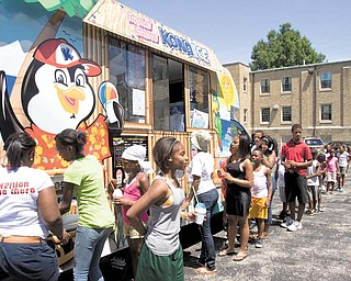 Children in the summer camp at Martin Luther Lutheran Church, 420 Clearmount Ave., Youngstown, line up for sno-cones from Tim Oswald's Kona Ice. The icy treat provided some relief from the heat of the 85-degree day.