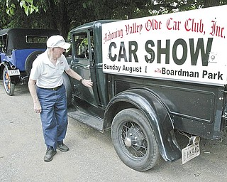 Joe Bush gets out of his 1931 Model A Ford truck, which carries the placard for the Mahoning Valley Olde Car Club car show Sunday in Boardman Park. Bush is a club member.