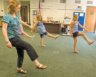 Julie Macomber , a volunteer at Hubbard Public Library, leads a dance lesson on the Cupid Shuffle line dance. In step are, from left, Chelsea Murphy, 8, partially obscured; Celeste Wilbois, 11; and Gabriella Torok, 9, all of Hubbard. Another dance lesson is planned next week.