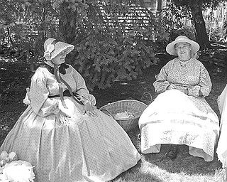 """What looks like two ladies who have stepped out of the past are really members of the Ohio Volunteer Infantry Co. D. They found a little shade to sit in as they displayed the clothing style of early American Women. The volunteers, part of a """"Living History Family,"""" will explain the roles of early families and other interesting facts for Niles Historical Society's """"Heritage Day,"""" which will be Sunday."""