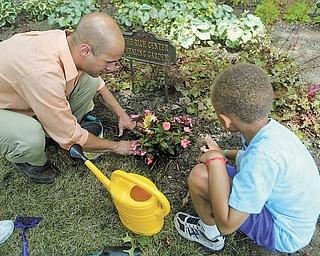 Teacher Casey Annko helps Jordan Walker, 7, of Niles as children at the Rich Center for Autism plant impatiens in the Outdoor Healing Garden. Working in the garden helps children strengthen muscles, improve motor skills and improve teamwork, program leaders say.