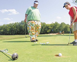 Tom Parteleno, left, works with Michael Curran, 9, of Hubbard, on the putting green at Parto's Golf Learning Center on Coitsville-Hubbard Road in Youngstown. Curran has been coming to the course for four years, originally once a week. He now comes almost every day, often times practicing for three hours at a time.