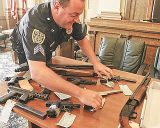 Det. Sgt Mike Lambert places a Smith and Wesson on a table. Youngstown and Warren officials announce the first wave of federal indictments to come out of the Violence, Gun Reduction Interdiction Program. Officers have confiscated 41 guns and indicted four people since the coordinated local and federal offensive against crime in the Mahoning Valley began July 4.