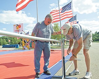 Greg Finnegan, left, and Dolph Carroll of Youngstown Christian School set up fl ags in preparation for Saturday's Gus Macker tournament in the parking lot at the Covelli Centre. Action begins early in the morning and lasts throughout the day.