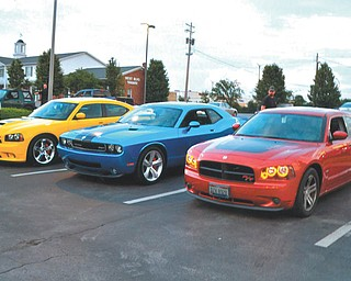 These three cars are owned by members of one family. The 2007 Dodge Charger Super Bee belongs to Chuck Sheffield; the 2010 Dodge Challenger is owned by Mary Sheffield; and the 2006 Daytona Go ManGo! Charger is their son Michael's. The picture was taken at the A&W in Boardman during the weekend of the LX Nationals.