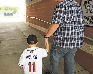 Luke Holko walks out with his dad Chad Holko at a Monday news conference announcing Luke Holko Day. Luke will be included in a team set of baseball cards given out during Sunday's Mahoning Valley Scrappers game.