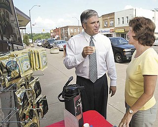 Girard Mayor James Melfi samples a specialty coffee as he chats with Peggy Magill, owner of Cards Candles and Collectibles on West Liberty Street in Girard. The mayor said specialty stores in the city have filled a niche and are weathering a tough economy.