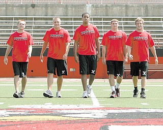 FEARSOME FIVE: Youngstown State University quarterbacks, from left, Marc Kanetsky, Kurt Hess, Najee Tyler, Patrick Angle and Ganon Hulea take the field at Stambaugh Stadium on Thursday during YSU Media Day. The five battling for the starter position as the Penguins prepare for their first season under new coach Eric Wolford.
