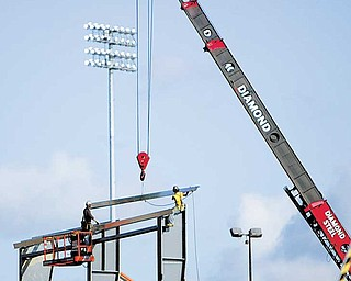 Ironworkers from Diamond Steel, Boardman, and Hively Construction, Canfi eld, put the first steel into place Monday for Youngstown State University's $10 million WATTS (Watson and Tressel Training Site) Center.