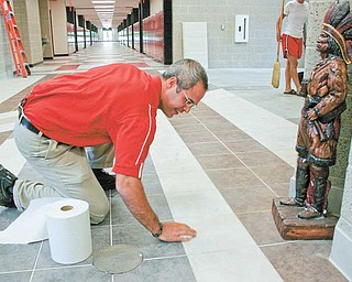 "William Ryser, senior high principal at the new Girard Junior/Senior High School, pitches in to clean the fl oor after an inadvertent spill as a statue of an Indian, the Girard mascot, ""oversees."" Ryser said he thinks the new building will inspire students and the sleek surroundings will enhance learning."
