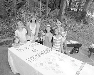 Daughters of Junior League of Youngstown members took park in a community service project while attending a membership Appreciation Day picnic recently at Mill Creek Park. Proud of their handiwork after leaving a colorful handprint on a banner prepared by the league are in front, from left, Elizabeth Siembida, Grace Aey, Lilly Aey, Ava Wilson, and Emilia Aey, in back, Isabel Aey.