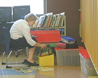 Carole Hoff organizes books in her third-grade classroom. In the new school, each classroom has five computers, including one for the teacher, and is equipped with a sound system so instructors can use lapel microphones.