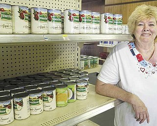Pat Mosley, vice president of the Salem Community Pantry, stocks shelves at the facility on 794 E. Third St. The pantry serves about 150 families a week.