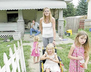 The Ben and Lynda Payne family returned from a camping trip recently to discover their West Side home severely damaged by a fire. In the background is Ben. Lynda spends time with their daughters, from left, Daisie, 2; Chelsea, 4; and SeaAnna, 7. The family is staying with a friend.