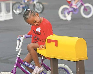 Victoria Balestrino, who begins kindergarten this fall, checks the mailbox Wednesday during the bicycle training station at safety village at North Elementary School in Poland.