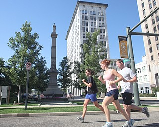 LESLIE CUSANO | THE VINDICATOR.Participants in the Panerathon run past the Man on the Monument in Downtown Youngstown. All money raised from the event will help build the Joanie Abdu Comprehensive Breast Care Center.