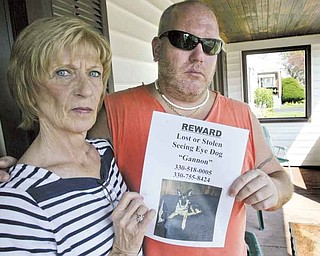 Sam Vona of Struthers, who is blind, and his mother, Jo Ann, hold one of the posters sheÕs put  up, seeking help and offering a reward to find Gannon, SamÕs seeing-eye dog, who ran off on Saturday..